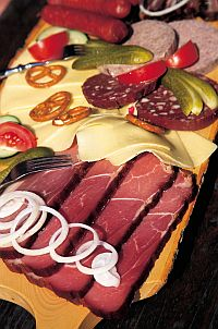 wooden board with ham, cheese and sausage