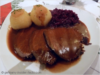 plate with sauerbraten, red cabbage and dumplings