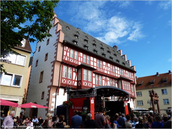 Food stalls and celebrating crowds in front of the historic house of goldsmiths at Lamboyfest in Hanau