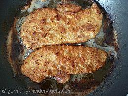 2 schnitzels in a frying pan